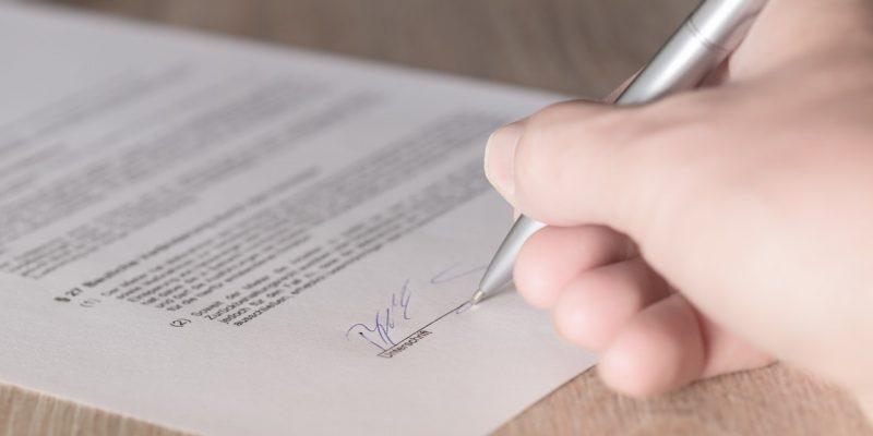 Eine Person unterschreibt gerade einen Sparvertrag