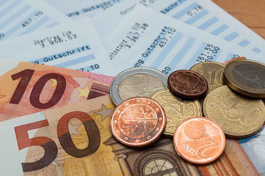 Kontoauszüge mit Geldscheinen und Münzen -bildlich